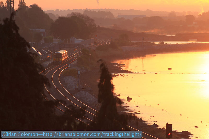 An Irish Rail 2600 pauses at Glounthaune. The car catches the glint of the sun. In a moment it will depart the station and head out onto the causeway that connects Fota Island. Canon EOS 7D with 200mm lens.