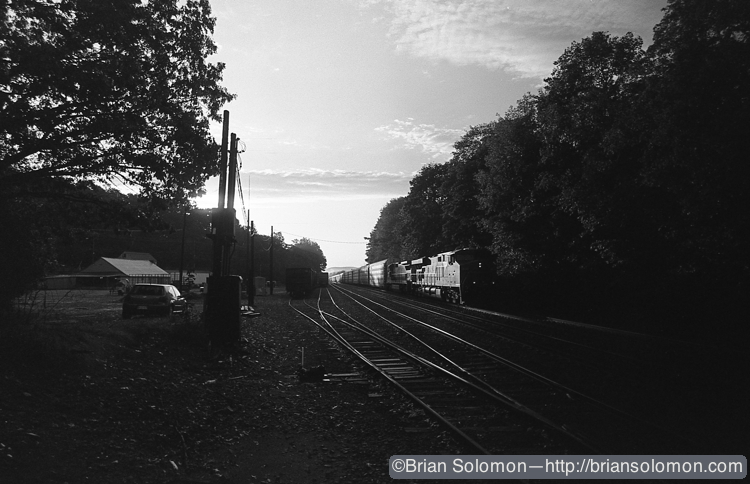 A westward freight catches the glint of the morning sun. Would the photo be better if the train was closer? Exposed on October 5, 2011.