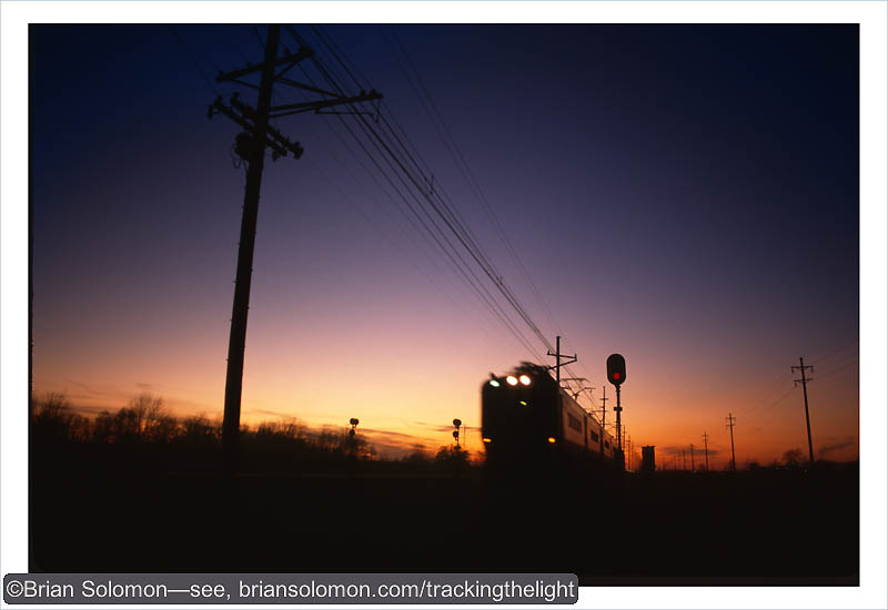 A Chicago, South Shore & South Bend electric races east away from the setting sun in October 1994. Exposed on Fujichrome using a Nikkormat FTN with 28mm lens.