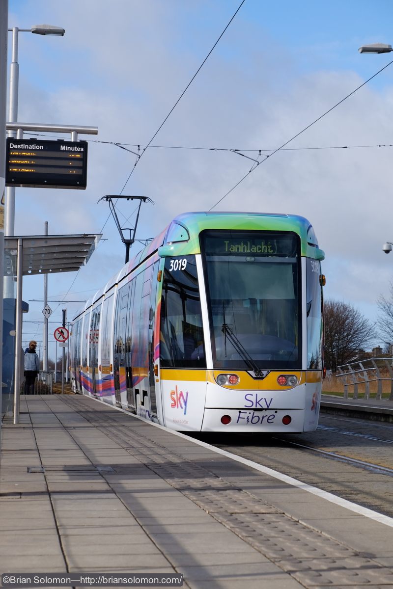 Trams in Dublin don't dally long; motors humming, this one accelerates away towards its next station stop. Fuji Film X-T1 digital camera; ISO 400.