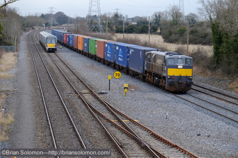 Irish Rail's IWT liner ambles toward Hazelhatch. An ICR is working uproad toward Dublin on the quad track mainline. Fuji X-T1. By using the tilting rear screen, I was able to hold the camera over my head and compose this scene in 'live view'.