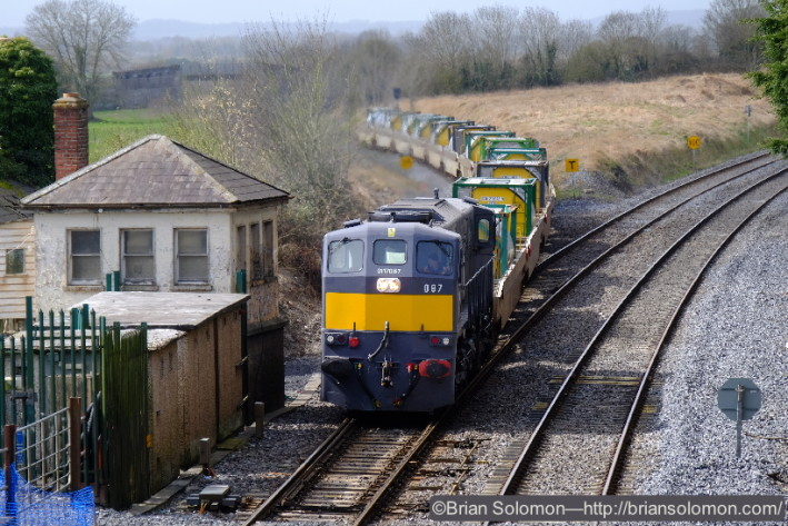 Freshly painted Irish Rail 087 leads the container pocket wagons working as the DFDS Liner on April 3, 2015. The old signal cabin at Cherryville Junction is many years out of service.