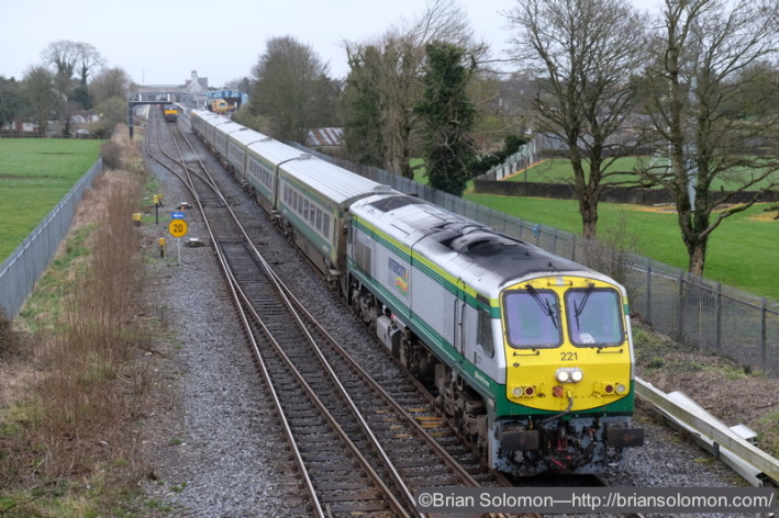 At 10:29 locomotive 221 with the 10 am Dublin-Cork Mark4 passes Kildare. The laden timber holds on the up-road waiting for a path.